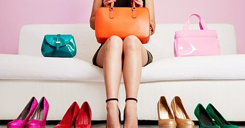 Woman sitting on lounge surrounded by bags and shoes