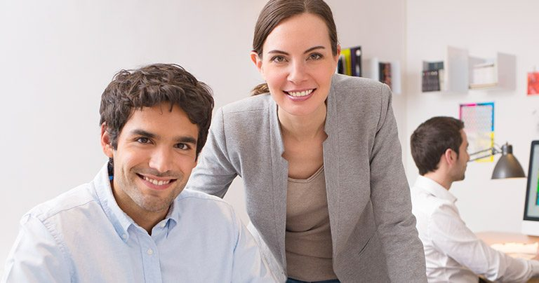Two smiling professionals working together in office