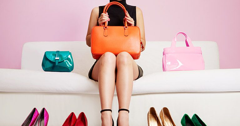 Woman sitting on lounge surrounded by shoes and bags