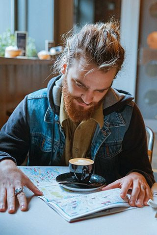 young man with man bun in a cafe with coffee