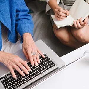 a photo of a hand using a computer and a woman writing for a UX agency in Sydney