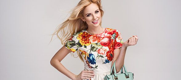 Fashionable woman posing in floral dress carrying handbag