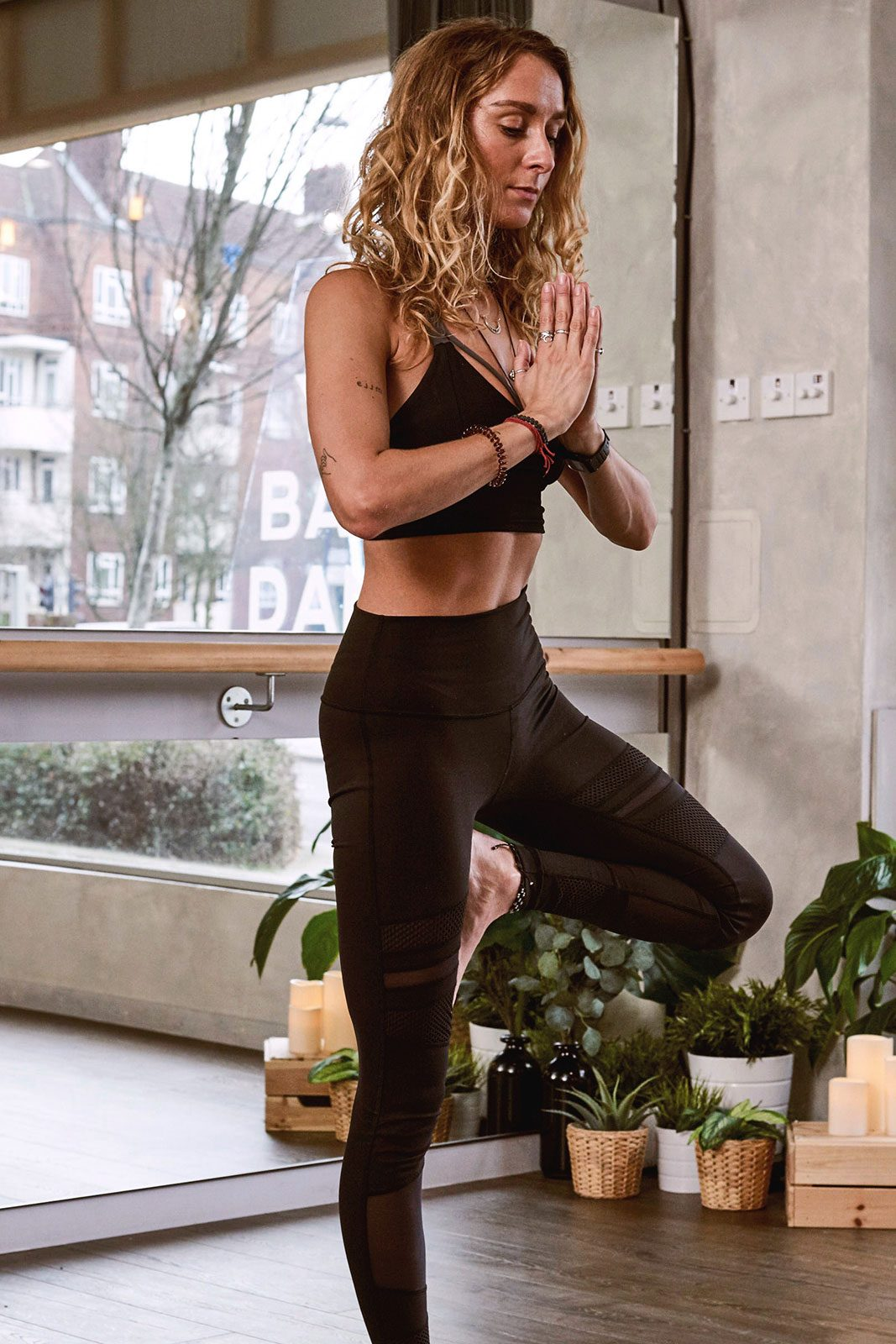 Yoga instructor with long hair, standing in a yoga posture