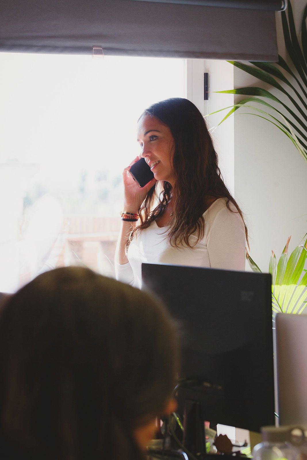 Professional woman in office and smiling on phone