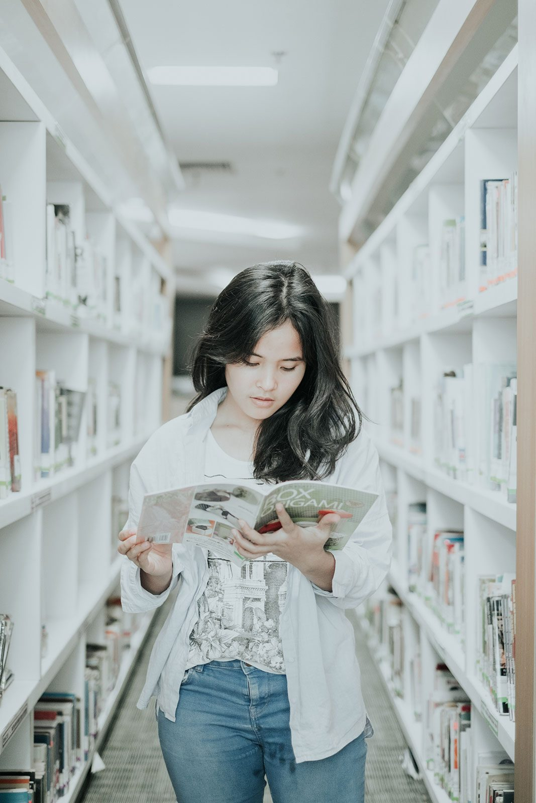 Female student in library reading a book