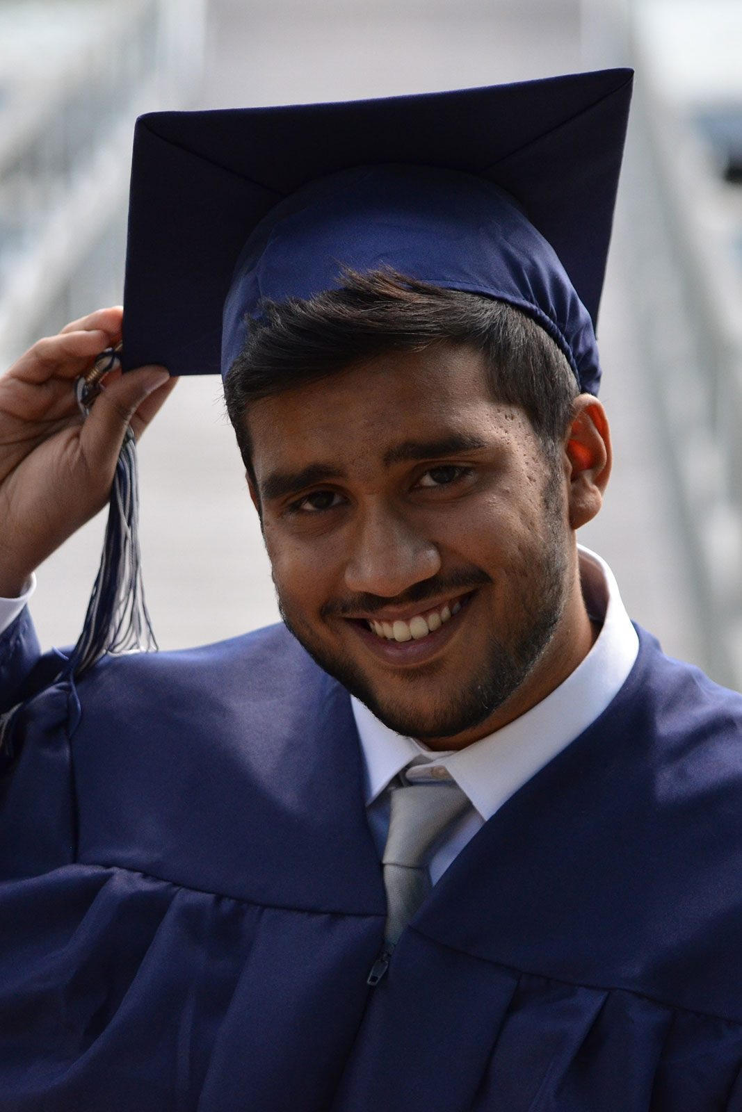 13. Graduate student smiling with gown on