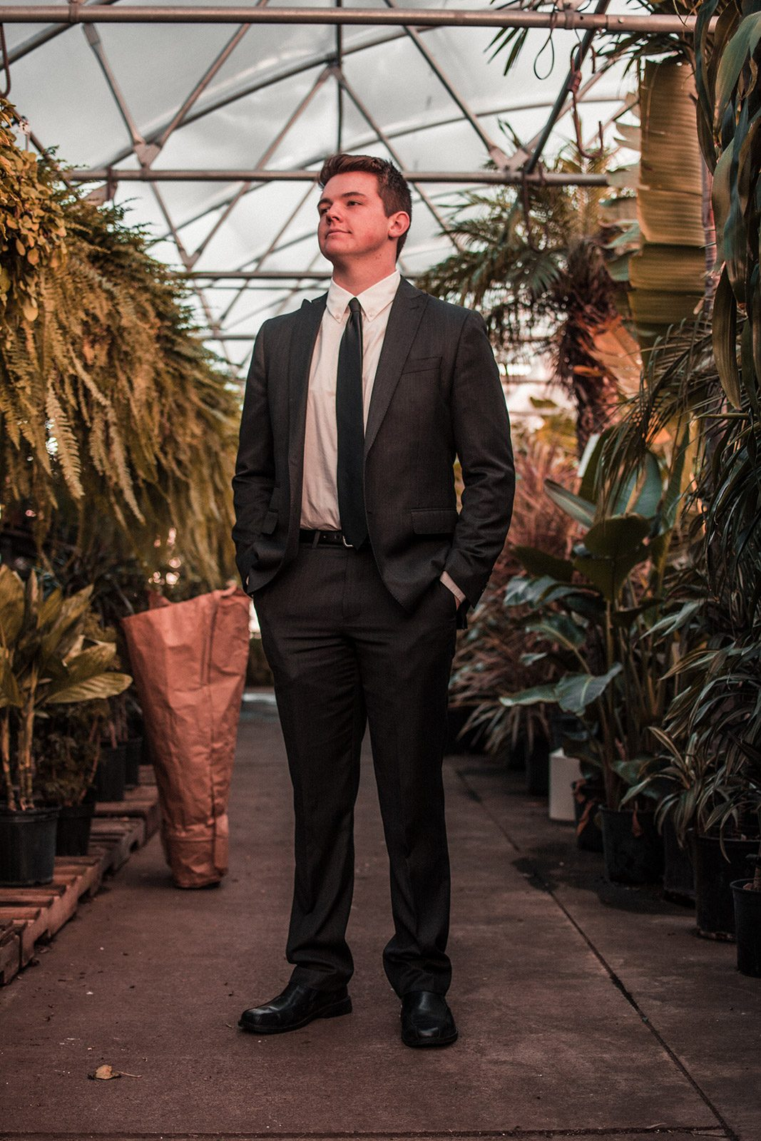 Young professional in a suit standing in a garden