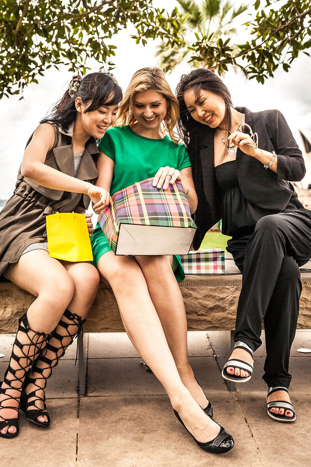 Three young woman looking through their shopping bags